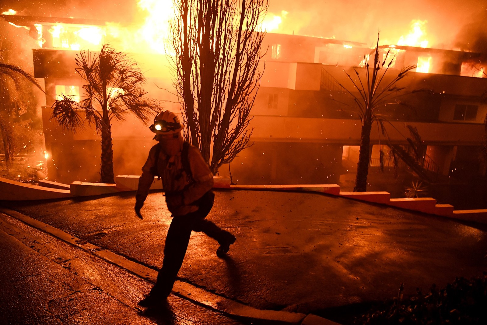 A firefighter at a burning apartment building in Ventura, where the Thomas fire charred 55,500 acres and forced 27,000 to flee. — Photograph: Michael Owen Baker/Los Angeles Times.