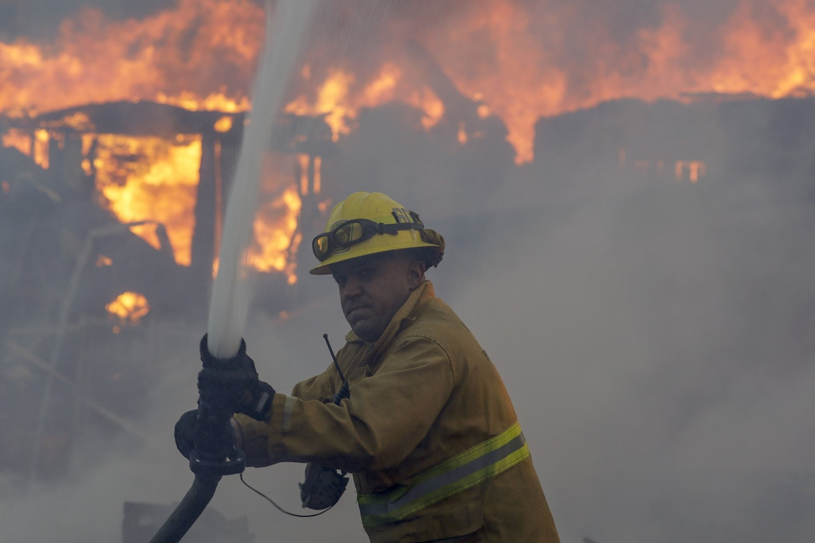 A firefighter works against the Creek fire in the Shadow Hills area of Los Angeles as a structure burns in the background. — Photograph: Irfan Khan/Los Angeles Times.