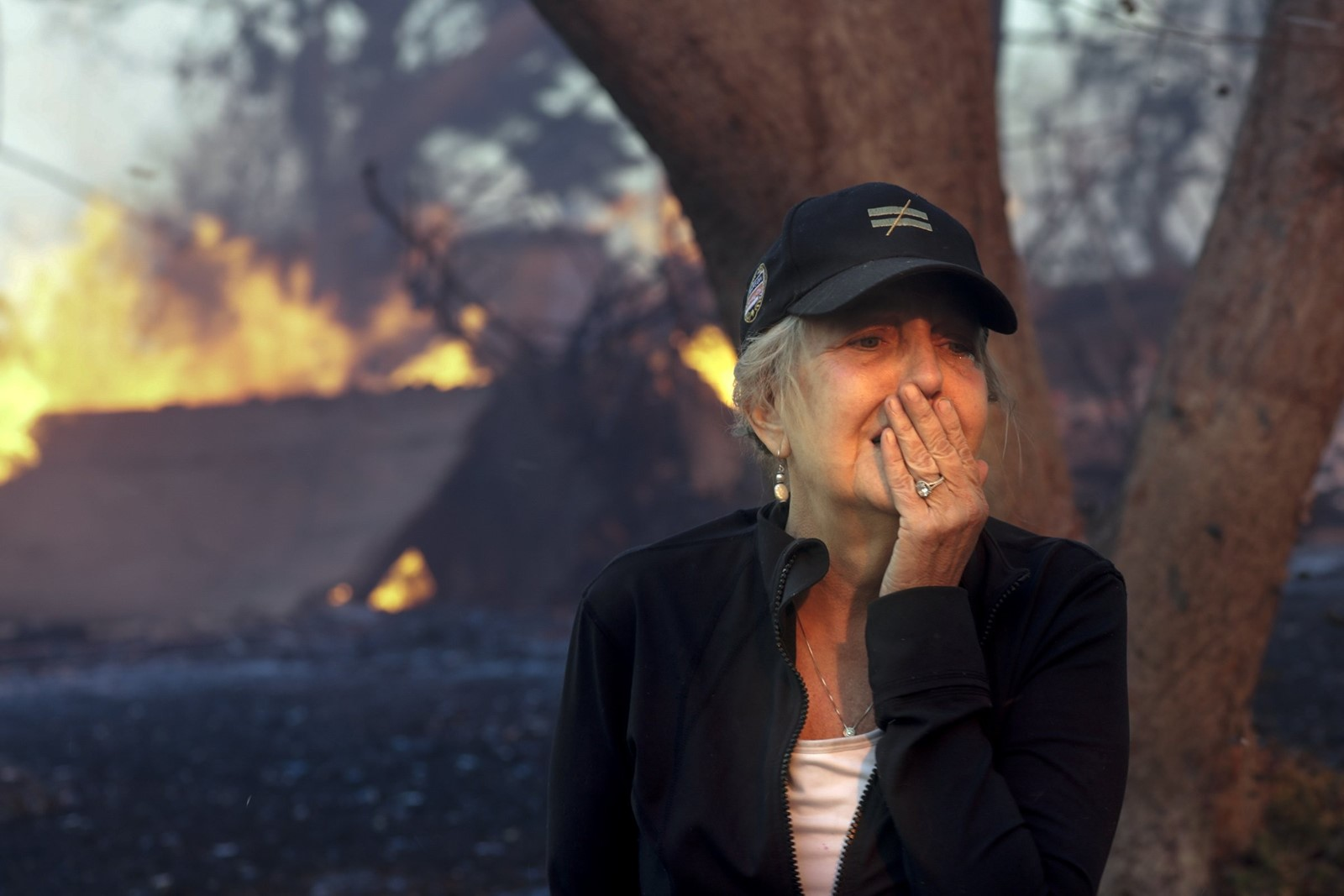 Judy Hofmann-Sanders watches as the Creek fire consumes her home on McBroom Street in L.A.'s Shadow Hills neighborhood on Tuesday. — Photograph: Irfan Khan/Los Angeles Times.