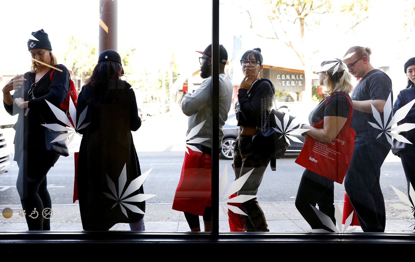 The reversal of a U.S. policy allowing leeway for state-sanctioned sales of marijuana could push banks to rethink their plans. Above, a line at MedMen dispensary in West Hollywood. — Photograph: Christina House/Los Angeles Times.