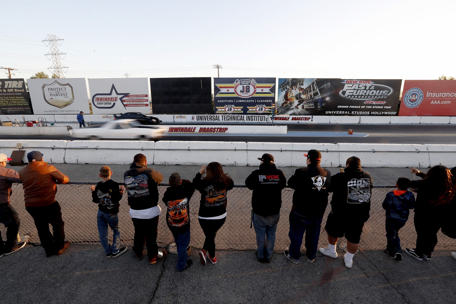 Channeled into a safe legal space away from the streets, fans watch drag races at Irwindale Speedway. — Photograph: Luis Sinco/Los Angeles Times.