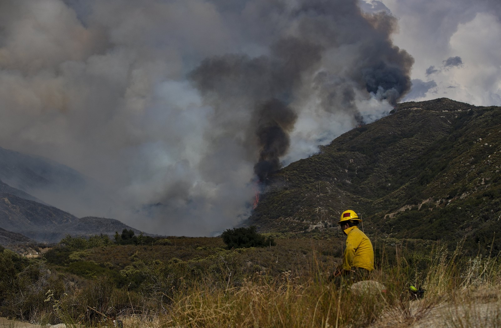 A firefighter keeps watch over the Cranston fire, crossing over Highway 74 toward Idyllwild. Riverside County sheriff's deputies ordered homes evacuated in Idyllwild, Apple Canyon, Lake Hemet, Mountain Center and Hurkey Creek. — Photograph: Gina Ferazzi/Los Angeles Times.