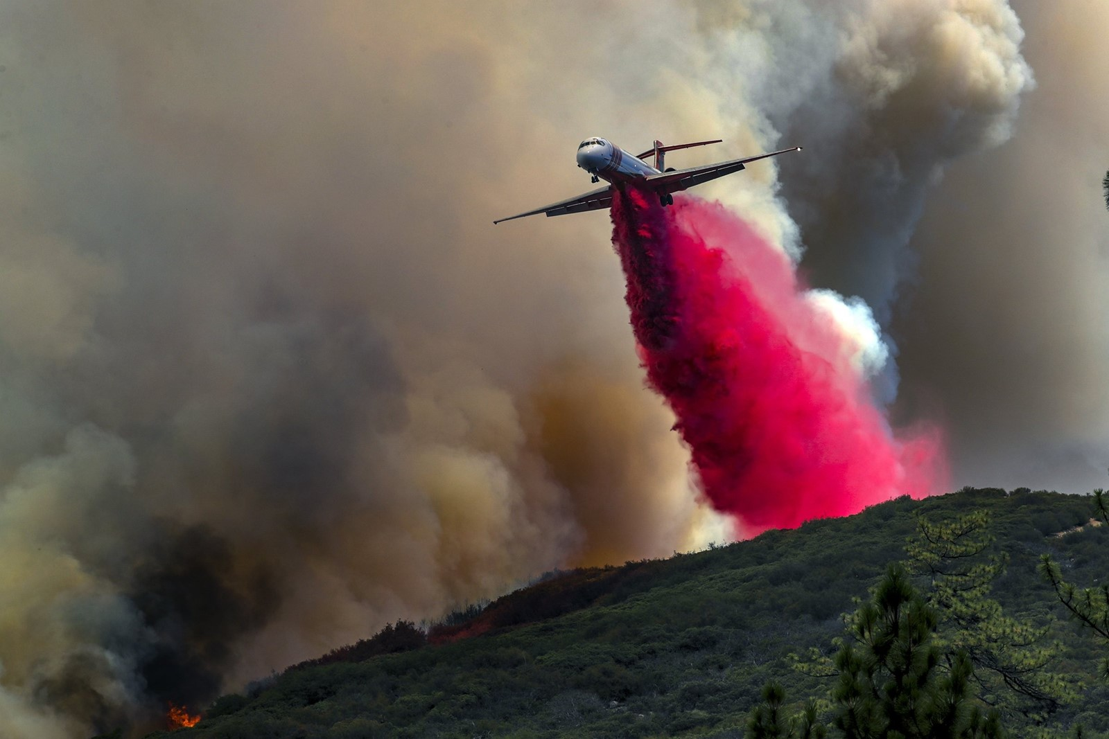 A plane, seen from Highway 74, drops retardant on the Cranston fire Thursday in Mountain Center. The fire was easily spotted by its billowy plumes of smoke. — Photograph: Irfan Khan/Los Angeles Times.