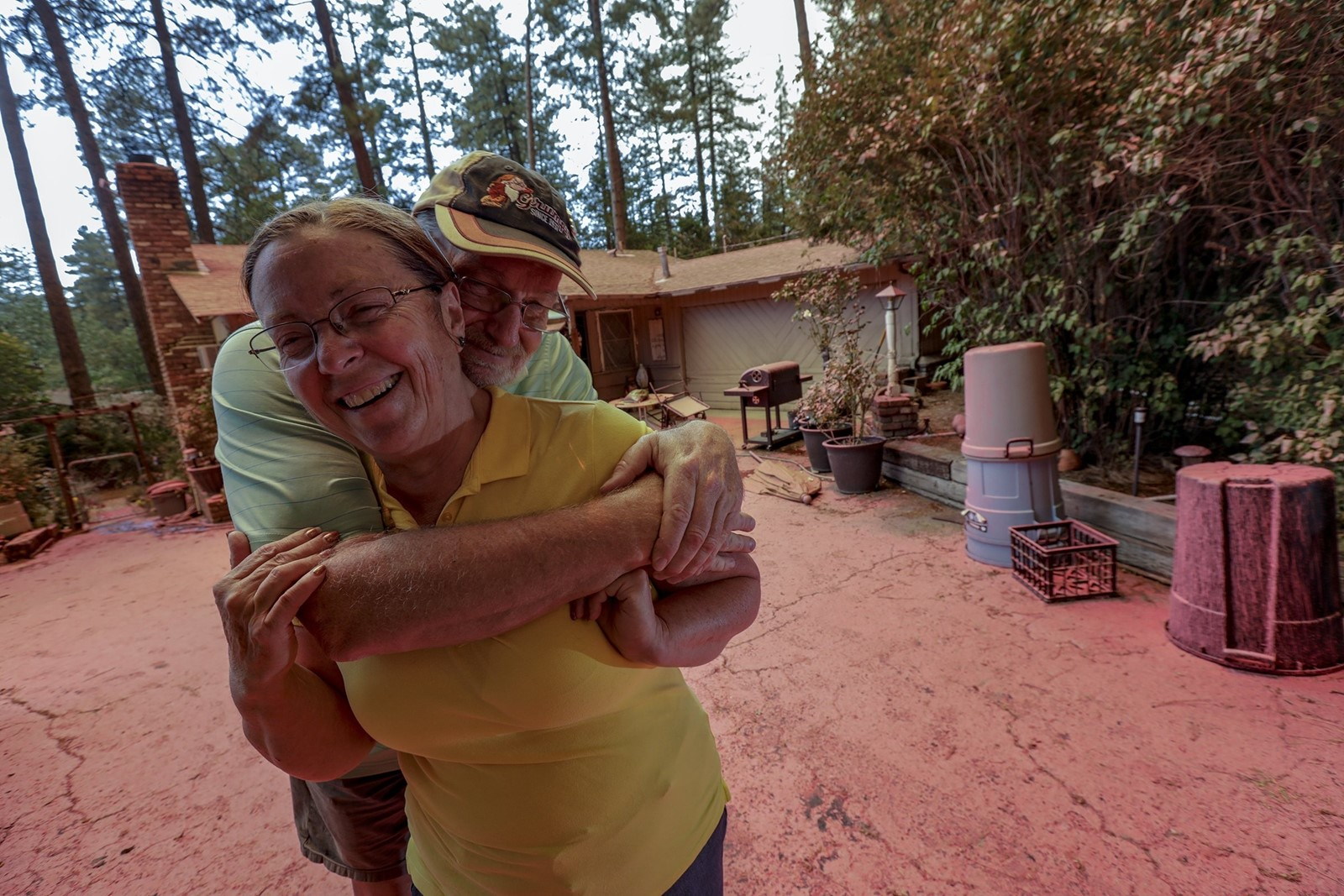 Steve and Suzanne Coffer, longtime residents of Idyllwild, rushed home on Wednesday to see their house on Deer Foot Lane coated in a pink fire retardant. — Photograph: Irfan Khan/Los Angeles Times.