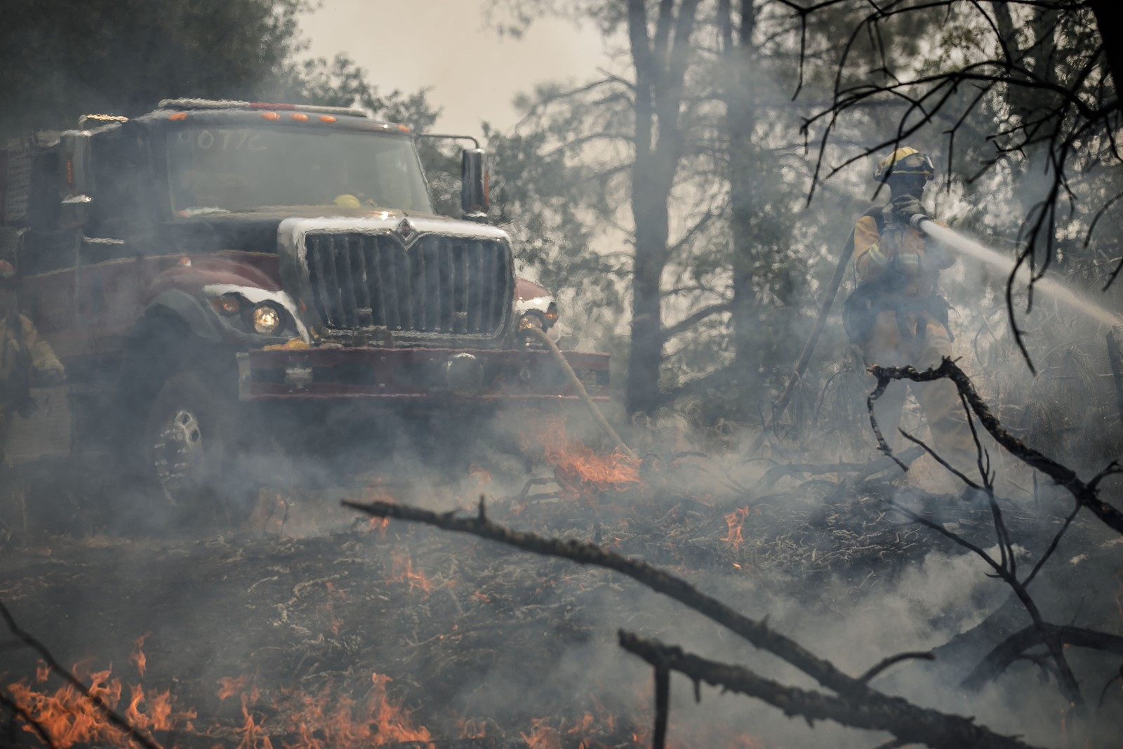Firefighters work to extinguish a blaze in an area outside Redding. A vehicle mechanical failure on Route 299 is said to have started the fire on Monday. — Photograph: Marcus Yam/Los Angeles Times.