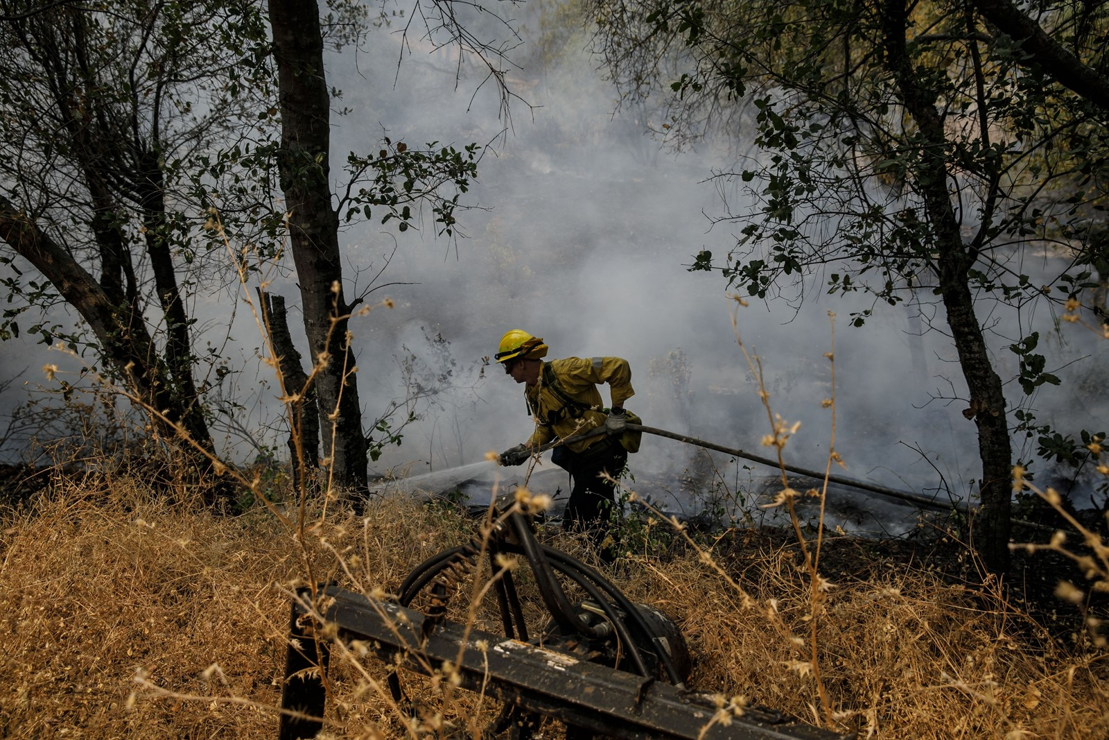 A firefighter from Los Angeles douses hot spots in the Carr fire near homes in Redding on Sunday. About 12,000 firefighters from within California are battling 17 wildfires burning over 200,000 acres across the state. — Photograph: Marcus Yam/Los Angeles Times.