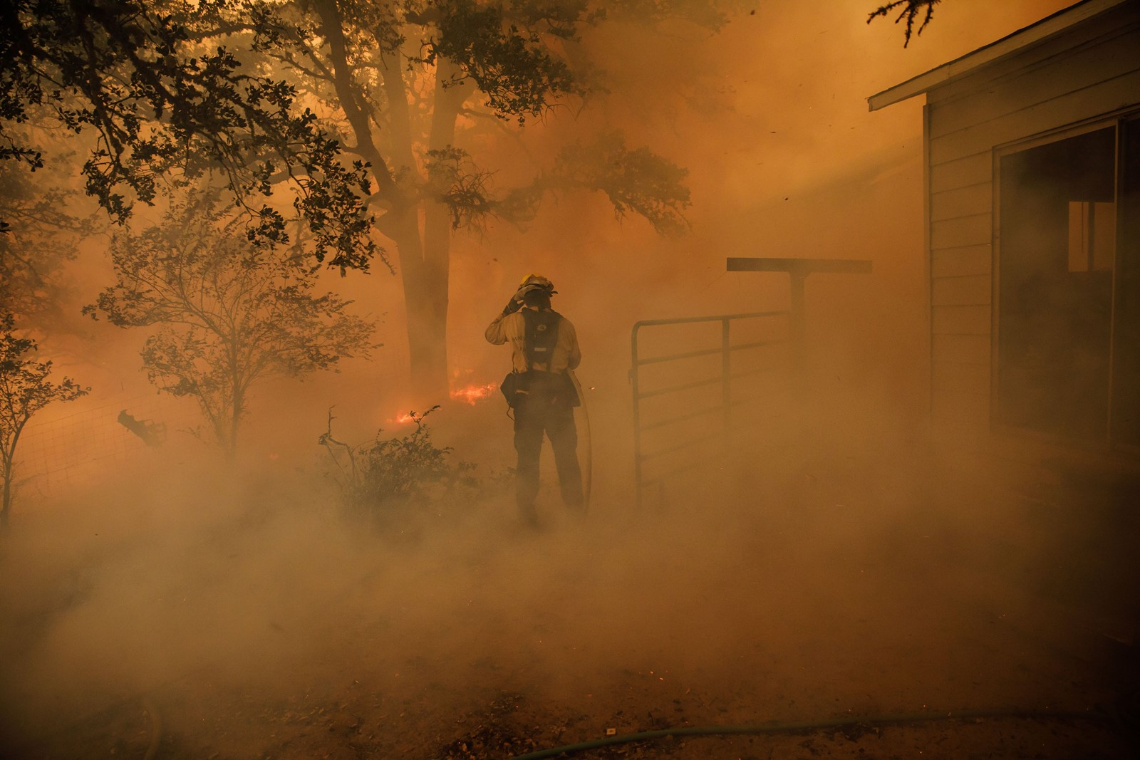 Firefighters near Lakeport in Mendocino County try to keep a home from being destroyed. A common thread in the California fires this year is extreme heat, the likes of which the state has never seen in the modern historical record. — Photograph: Marcus Yam/Los Angeles Times.