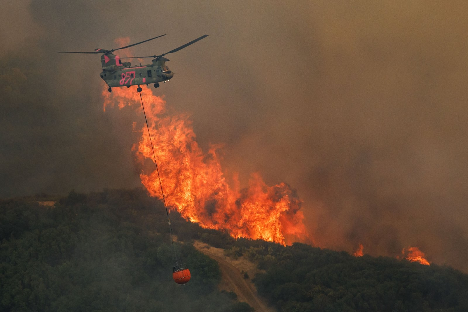 A helicopter drops water on the River fire, one of two blazes in Mendocino County, California. Together the two fires have burned more than 80,000 acres since Friday and neither is more than 12% contained. — Photograph: Marcus Yam/Los Angeles Times.