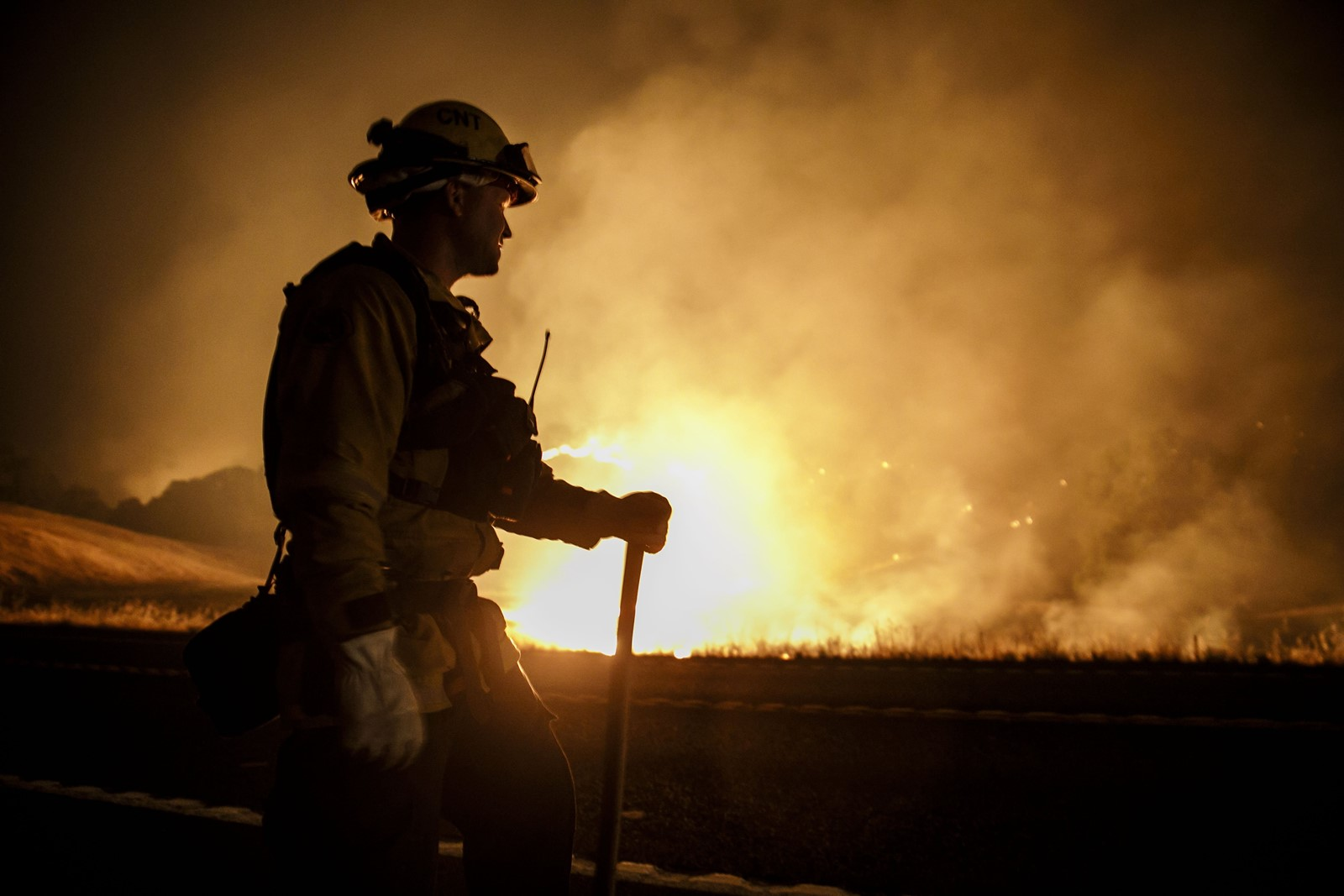 A firefighter monitors a controlled burn in Upper Lake, California, on Tuesday. The Mendocino Complex fire is one of about 100 fires burning in the West. — Photograph: Marcus Yam/Los Angeles Times.