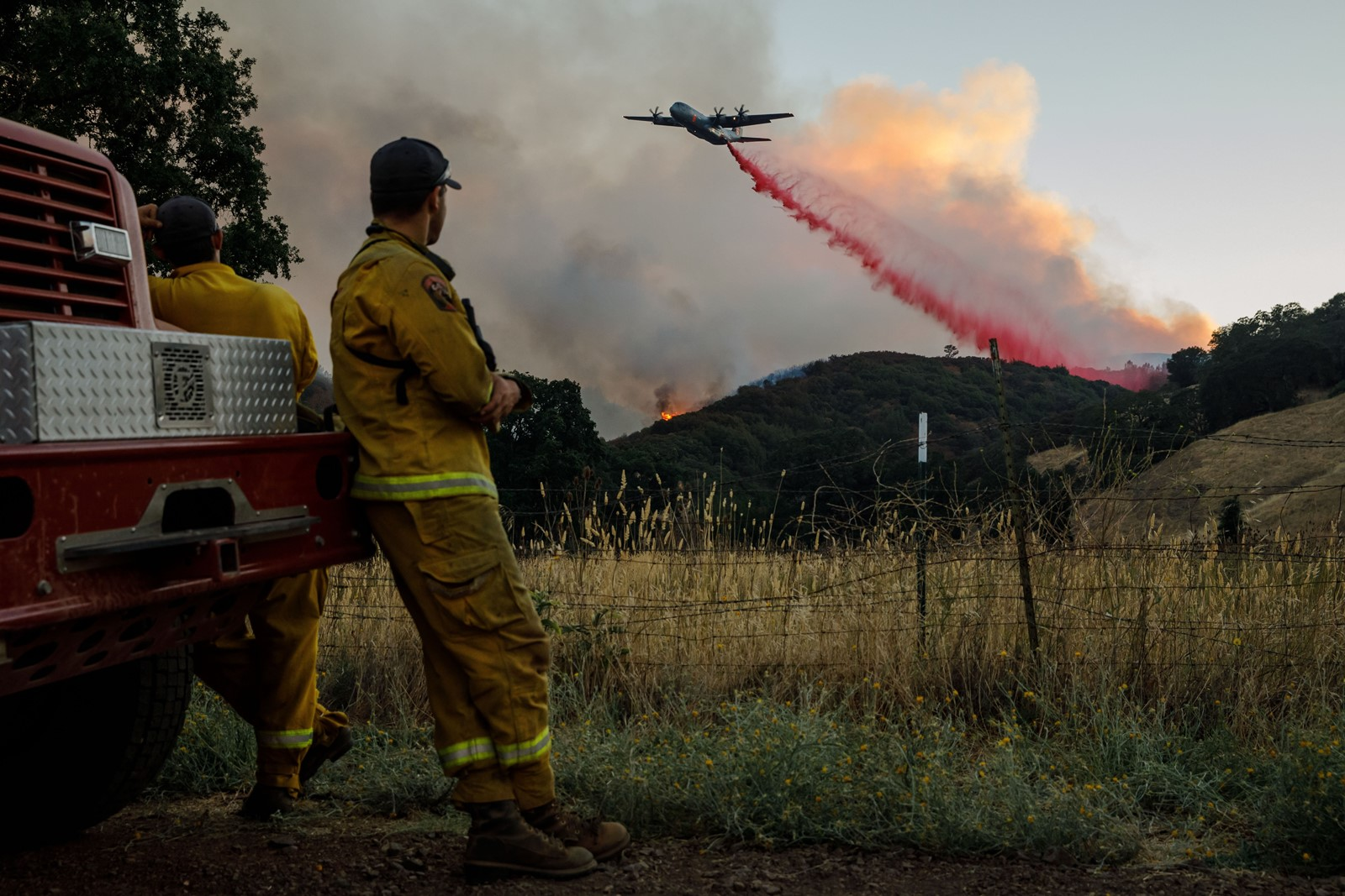 Firefighters watch as air tankers drop flame retardant ahead of the River fire in Lakeport, California, on Wednesday. The blaze, one of 16 large wildfires burning across the state, was 33,398 acres and 38% contained. — Photograph: Marcus Yam/Los Angeles Times.