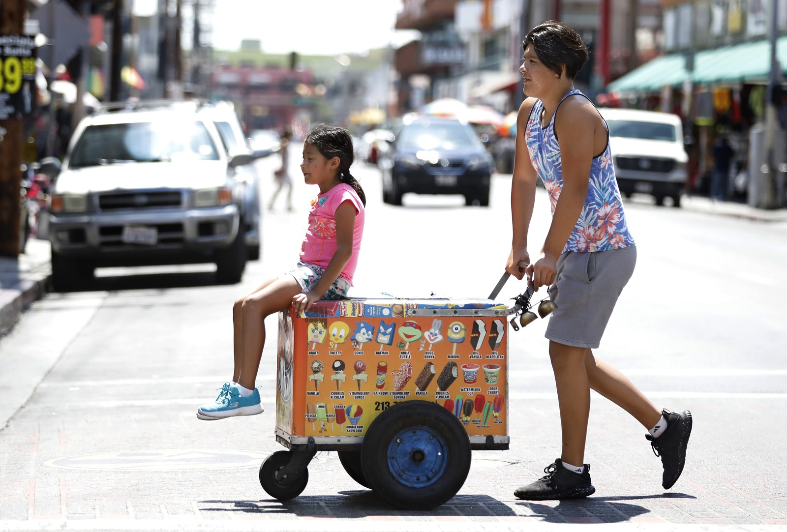 Adrian Valdivia gives Acacia Valencia a ride on an ice cream cart Wednesday in downtown Los Angeles, which endured its third-hottest July on record. — Photograph: Photograph: Mel Melcon/Los Angeles Times.