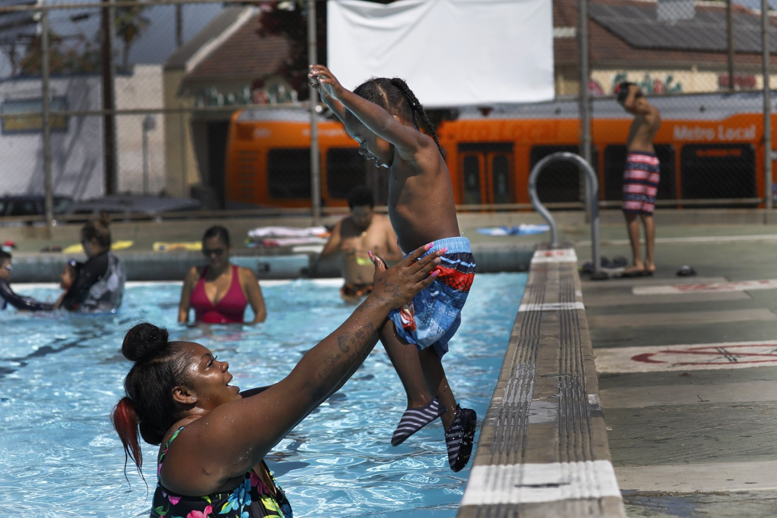 Ashley Moore plays in the pool with her 2-year-old son, Alijah, in Highland Park on Wednesday. — Photograph: Francine Orr/Los Angeles Times.