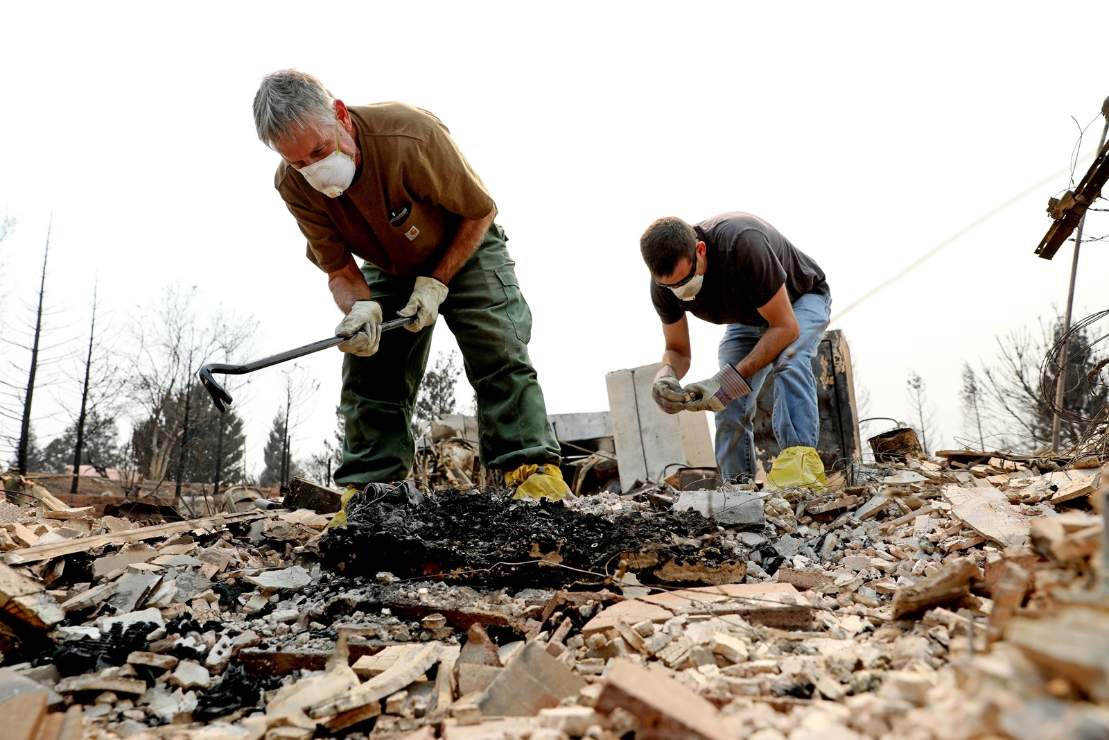 Dan Kissick, left, and his son Jeff sift through the remains of his home in Redding, California, lost to the Carr fire. — Photograph: Gary Coronado/Los Angeles Times.