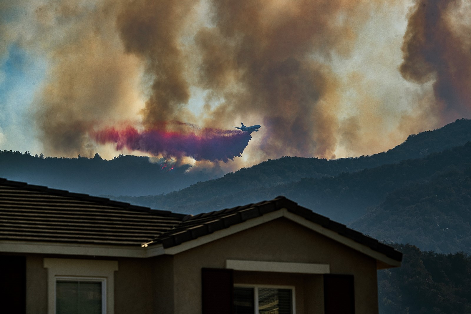 An air tanker drops fire retardant on the Holy fire burning in Cleveland National Forest above a home in Lake Elsinore on Tuesday afternoon. The fast-moving fire broke out on Monday, burning more than 3,000 acres and forcing evacuations in two Orange County canyons. — Photograph: Allen J. Schaben/Los Angeles Times.