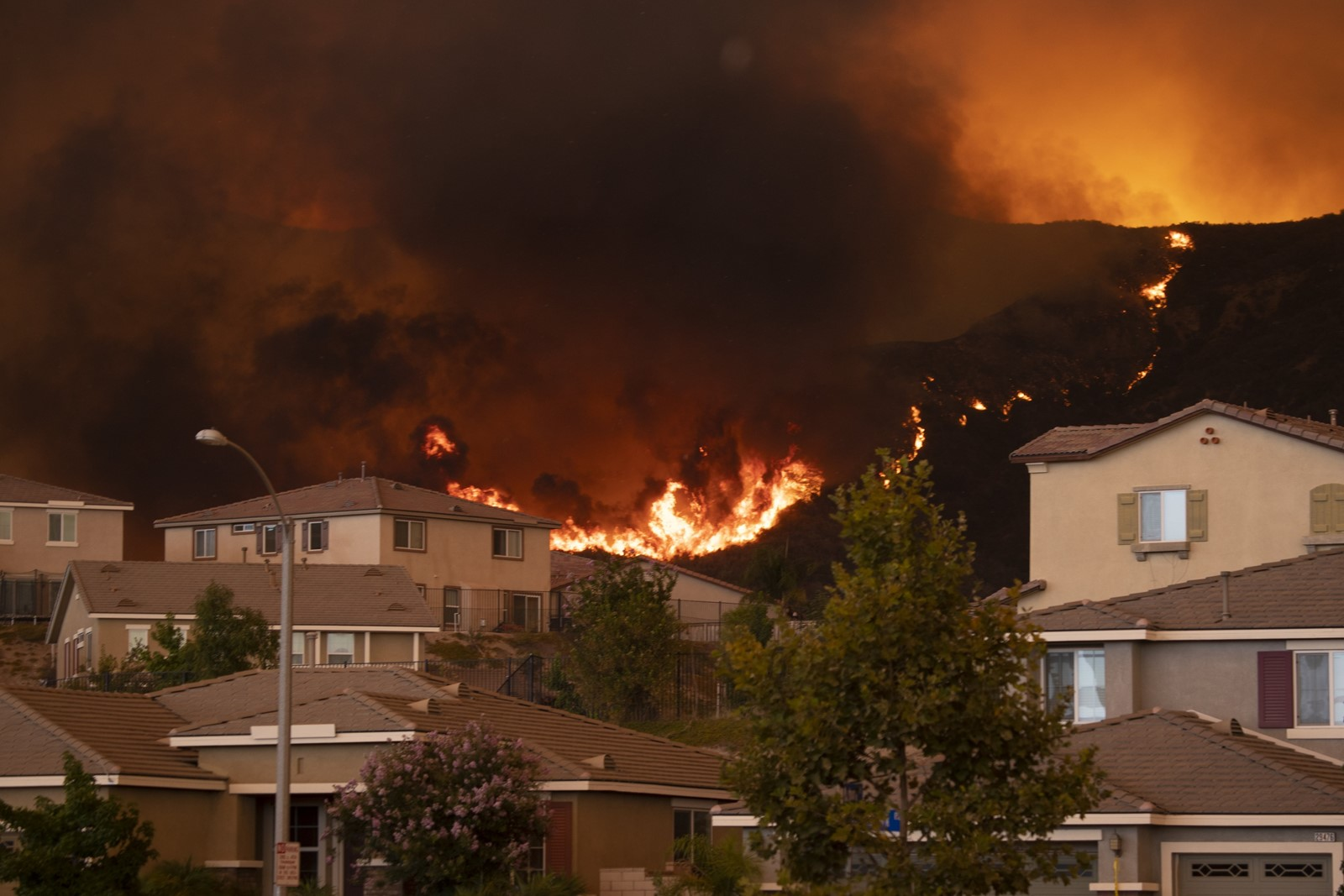 Flames approach homes in the McVicker Canyon neighborhood of Lake Elsinore on Wednesday. The growth of the Holy fire came on another day of record high temperatures in parts of Southern California. — Photograph: Allen J. Schaben/Los Angeles Times.