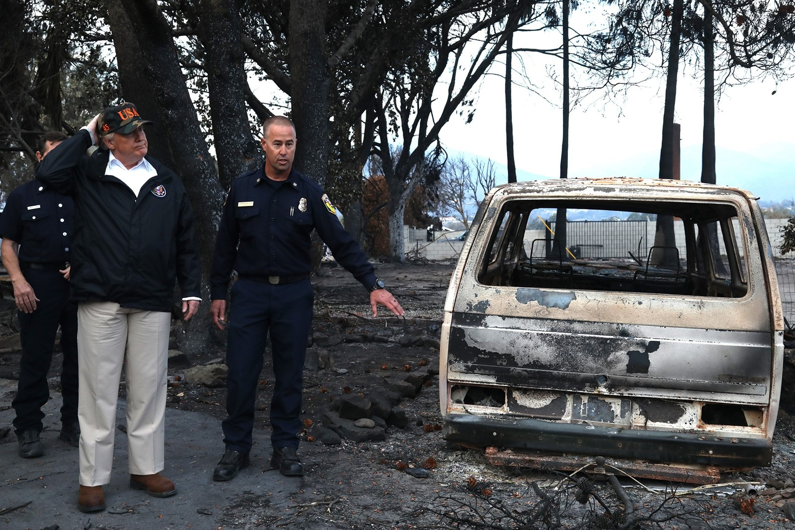 "Nick Schuler, deputy chief of the California Department of Forestry and Fire Protection, guides Trump through a Malibu neighborhood razed by the Woolsey fire. The president said he would help California ""100%"". — Photograph: Genaro Molina/Los Angeles Times."