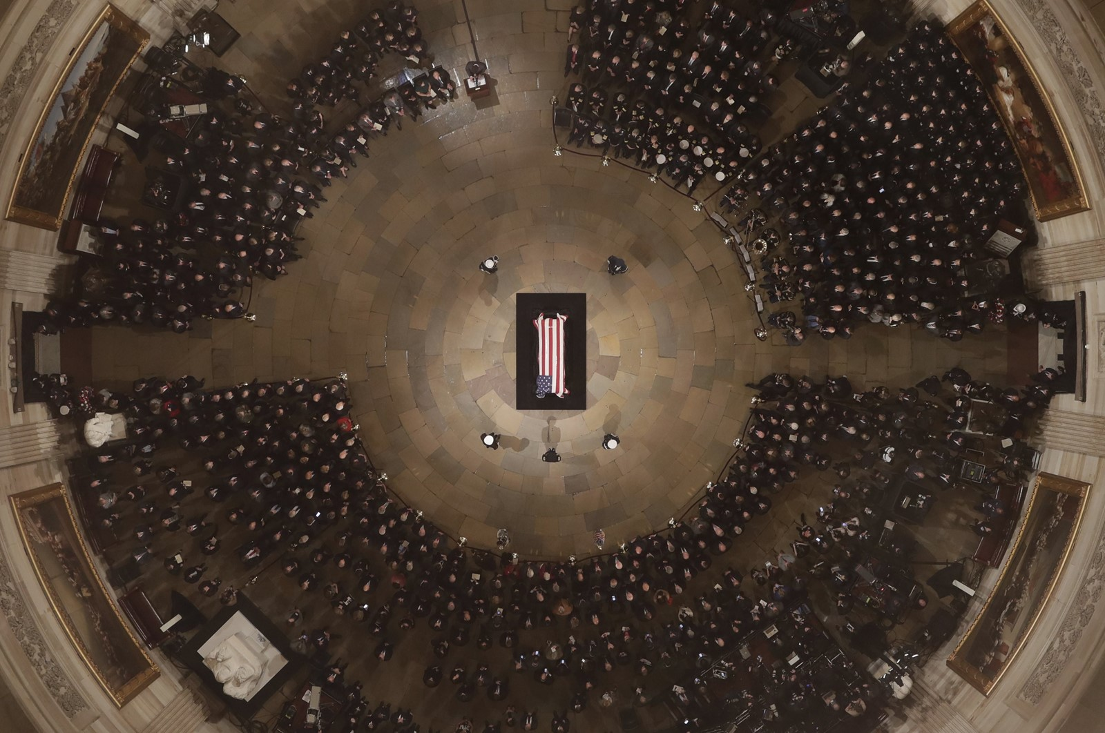 Former President George H.W. Bush lies in state in a flag-draped casket before a crowd of mourners in the U.S. Capitol Rotunda. — Photograph: Morry Gash/Pool Photo.