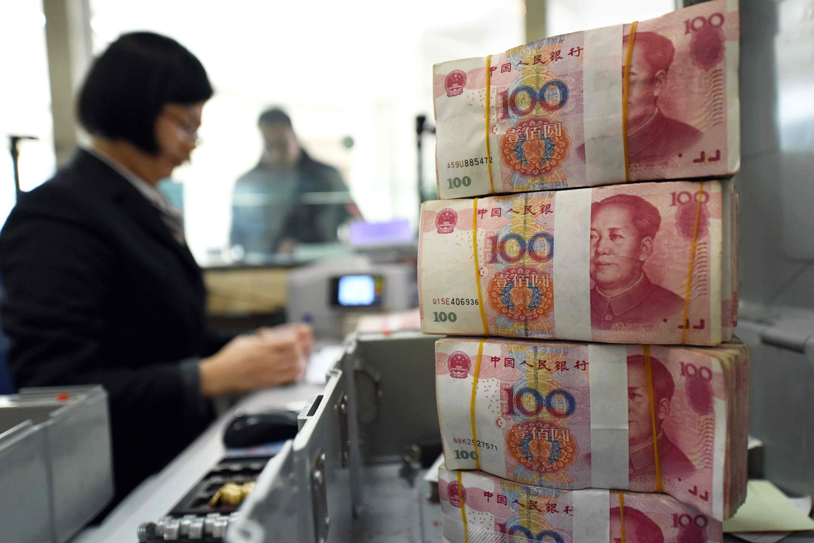 A bank employee counts 100-yuan notes in Lianyungang, in eastern China's Jiangsu province. — Photograph: Agence France-Presse/Getty Images.