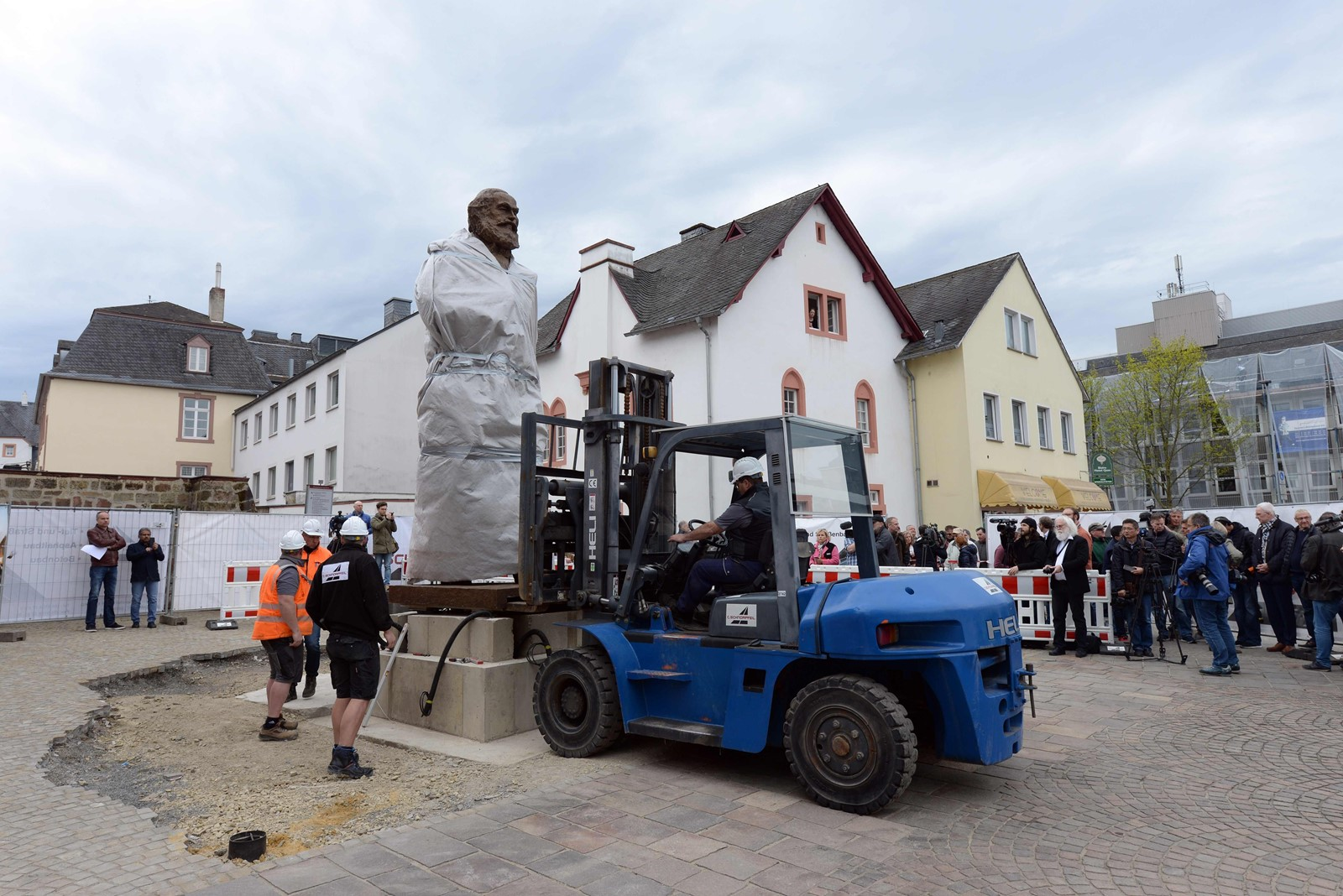 Workers install a statue of Karl Marx in Trier, Germany, which is planning a year of events to celebrate the founding father of communism. The fact that the statue is a gift from China has only added to the controversy. — Photograph: Harald Tittel/Agence France-Presse/Getty Images.