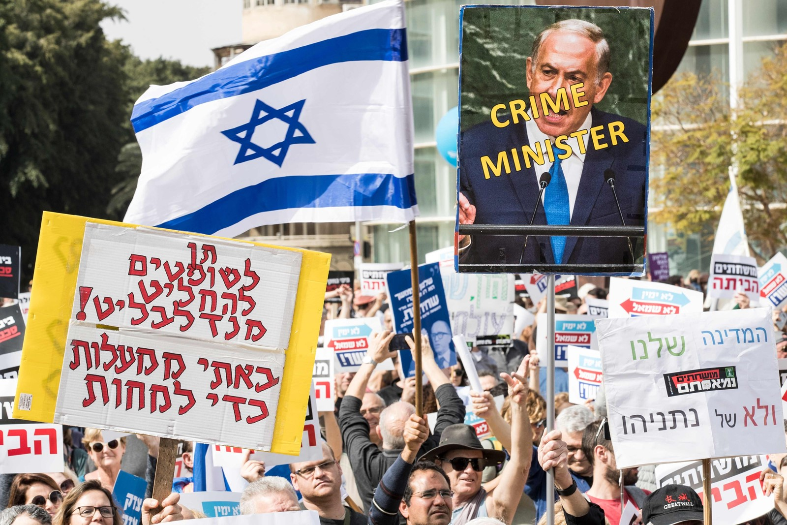Israelis protest in Tel Aviv on Friday against Prime Minister Benjamin Netanyahu after police recommended he be indicted on several corruption charges. — Photograph: Jack Guez/Agence France-Presse/Getty Images.