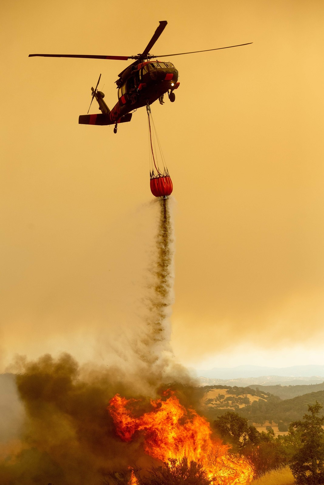 A helicopter drops water on the Ranch fire, which is part of the Mendocino Complex fire, near Clearlake Oaks, California, on Sunday. The erratic blaze has burned more than 266,000 acres and 68 homes in 10 days. — Photograph: Noah Berger/Agence France-Presse/Getty Images.