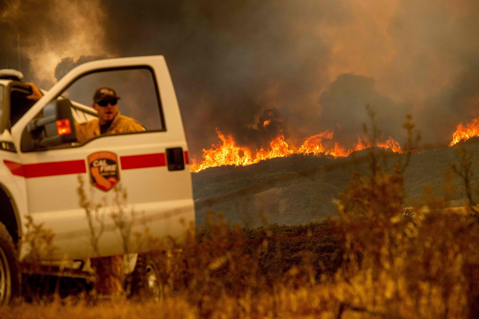 Battalion Chief Matt Sully directs firefighting operations near Clearlake Oaks, California, on Sunday as the Mendocino Complex fire grew to 266,000 acres. It's being spread by shifting winds and brittle-dry vegetation. — Photograph: Noah Berger/Agence France-Presse/Getty Images.