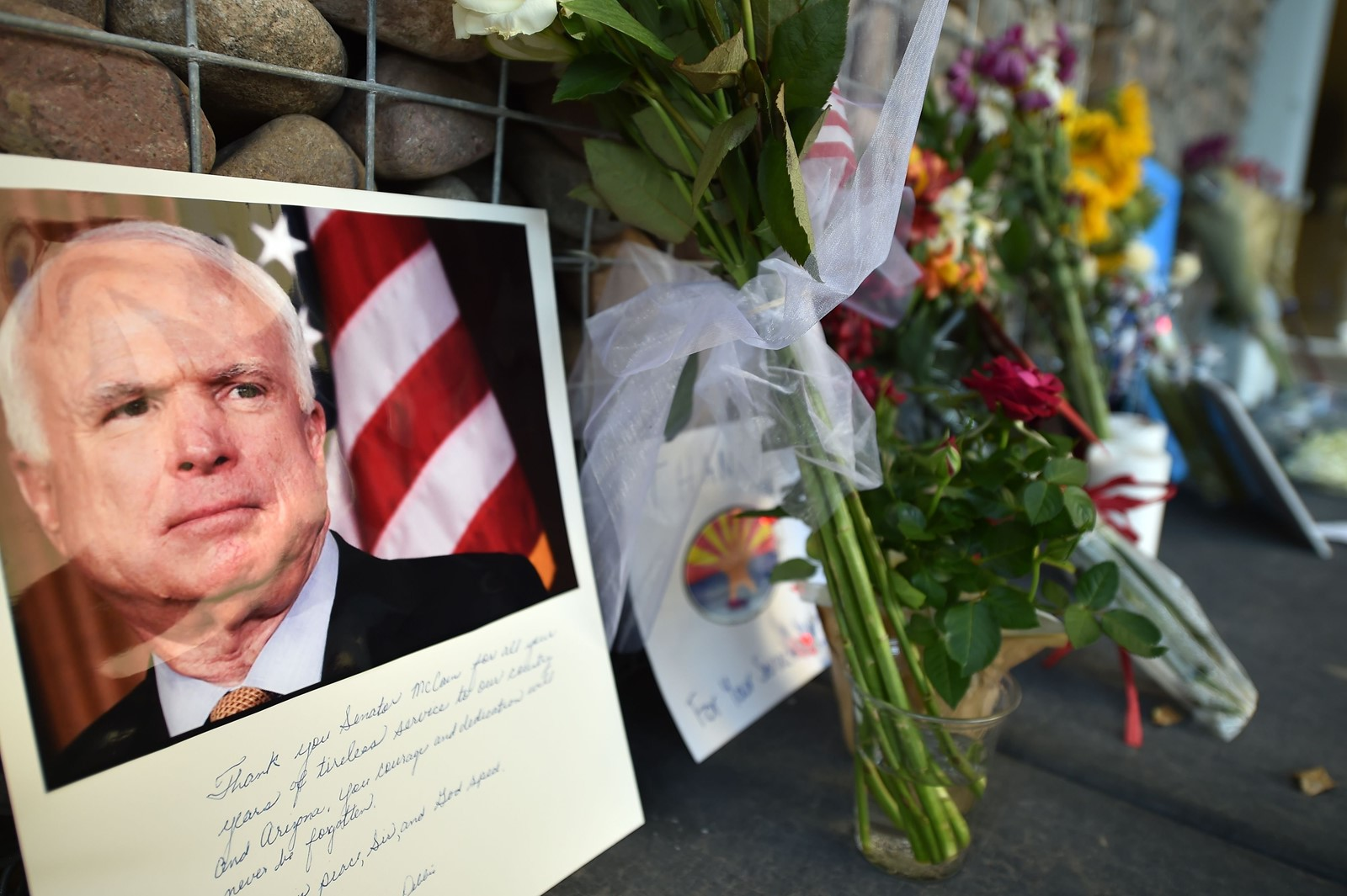 Flowers and cards for Senator John McCain sit outside his office in Phoenix. McCain let it be known that he did not want President Trump at his funeral. — Photograph: Robyn Beck/Agence France-Presse/Getty Images.
