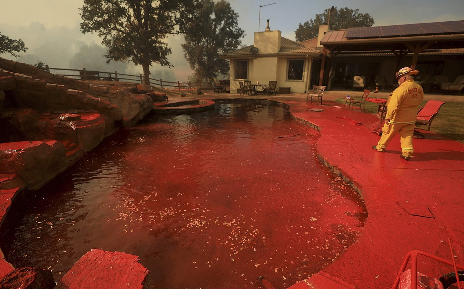Fire retardant coats a pool in Lake County on Thursday. Winds threatened to push the Ranch fire south, spurring evacuations in Lake and Colusa counties. — Photograph: Kent Porter/Press Democrat.
