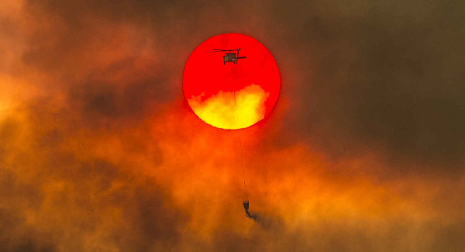 A firefighting helicopter drops water near Redding, California, where the Carr fire erupted last week amid triple-digit temperatures. — Photograph: Hector Amezcua/Sacramento Bee.