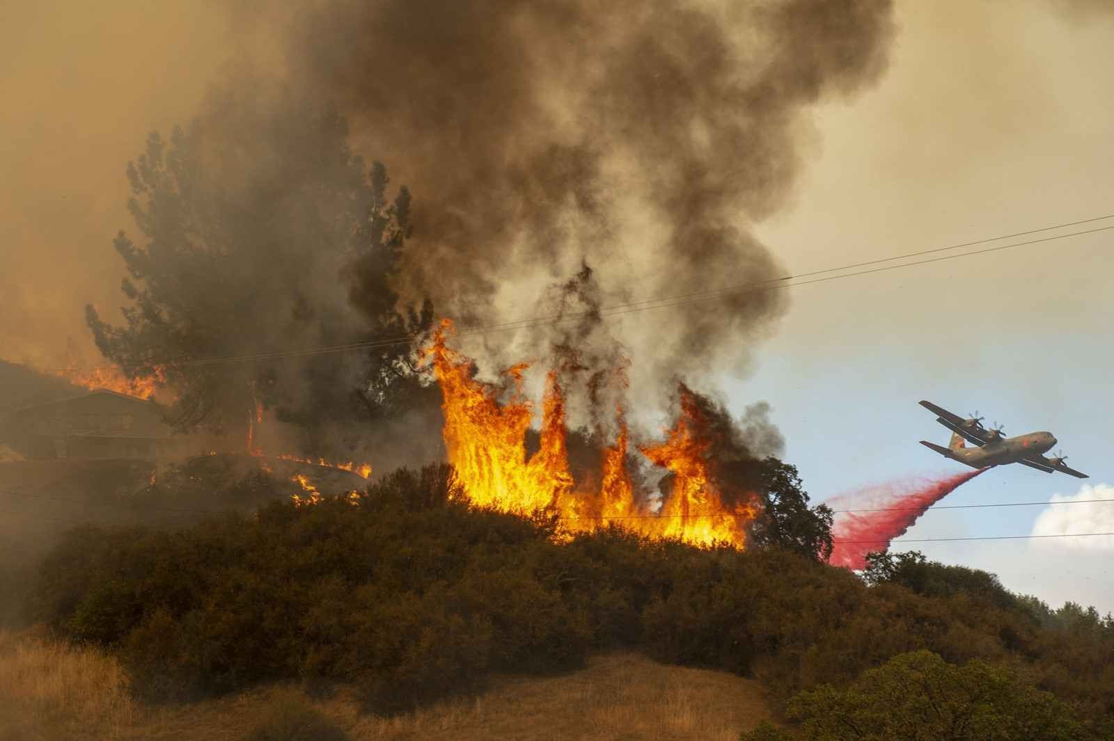 A plane drops fire retardant near a home west of Lakeport, California. A pair of wildfires in Medocino County exploded to more than 68,000 acres. — Photograph: Jose Luis Villegas/Sacramento Bee.