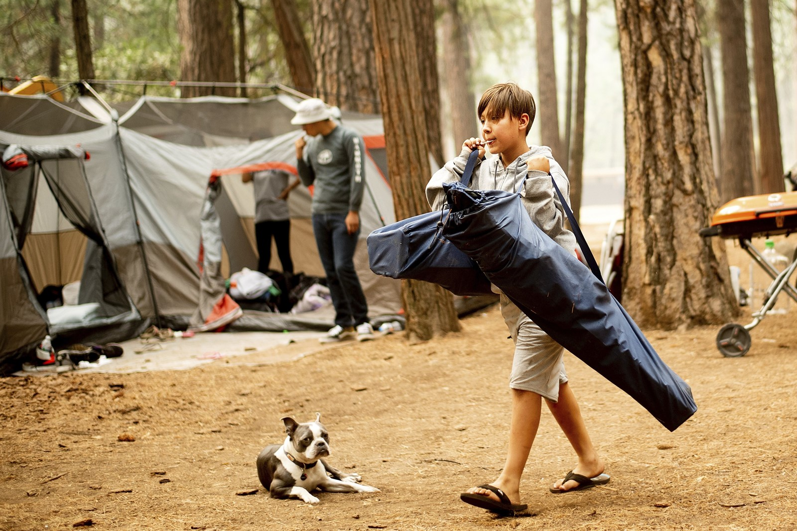River Martinez breaks camp at Yosemite park on Wednesday. The deadly Ferguson fire continued to rage near the park, and visitors had to leave by noon. — Photograph: Noah Berger/Associated Press.