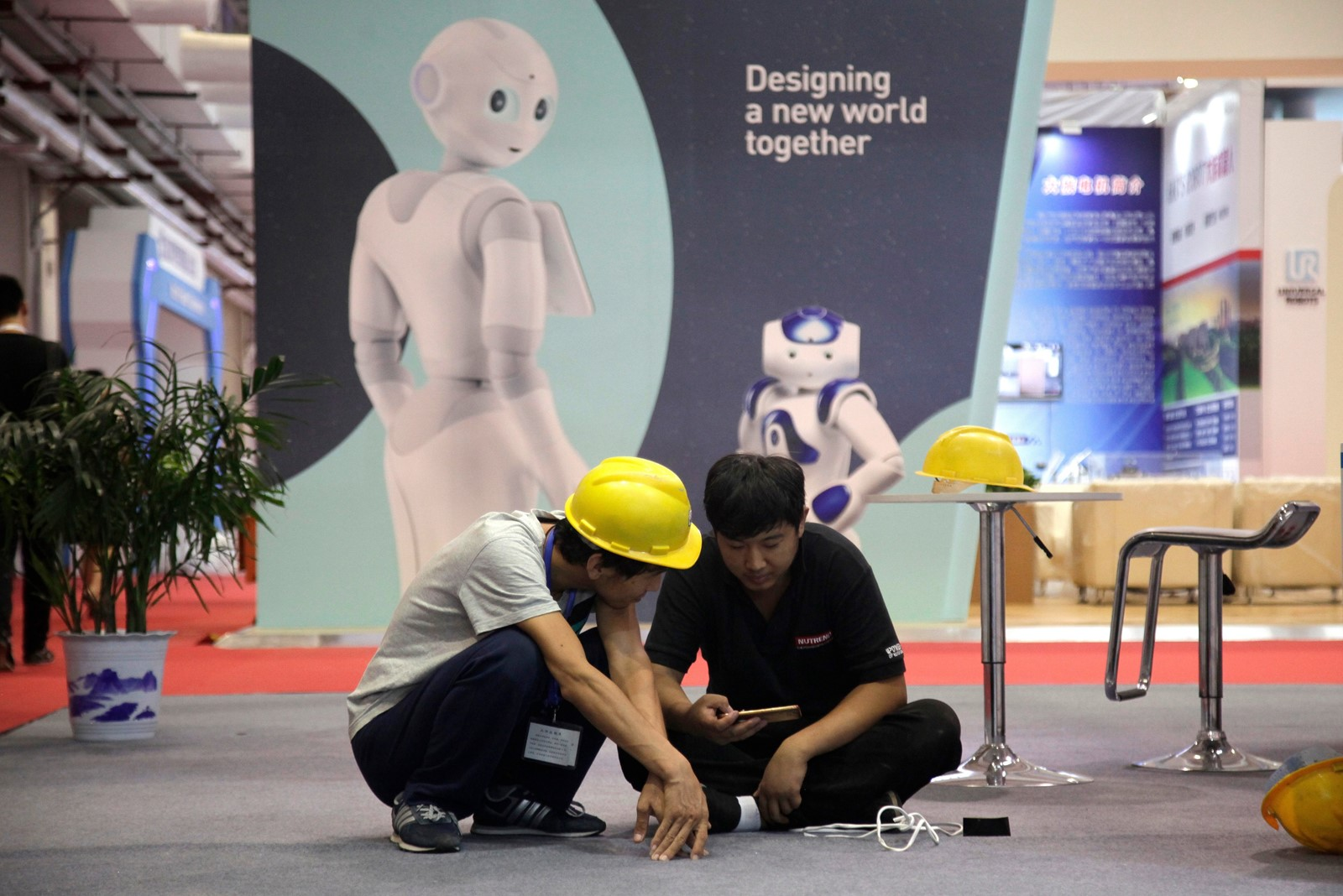 "Workers prepare for the World Robot Conference in Beijing last year. ""Made in China 2025"" aims to transform the country from a labor-intensive economy into one focused on products like robots and electric cars. — Photograph: Fu Ting/Associated Press."