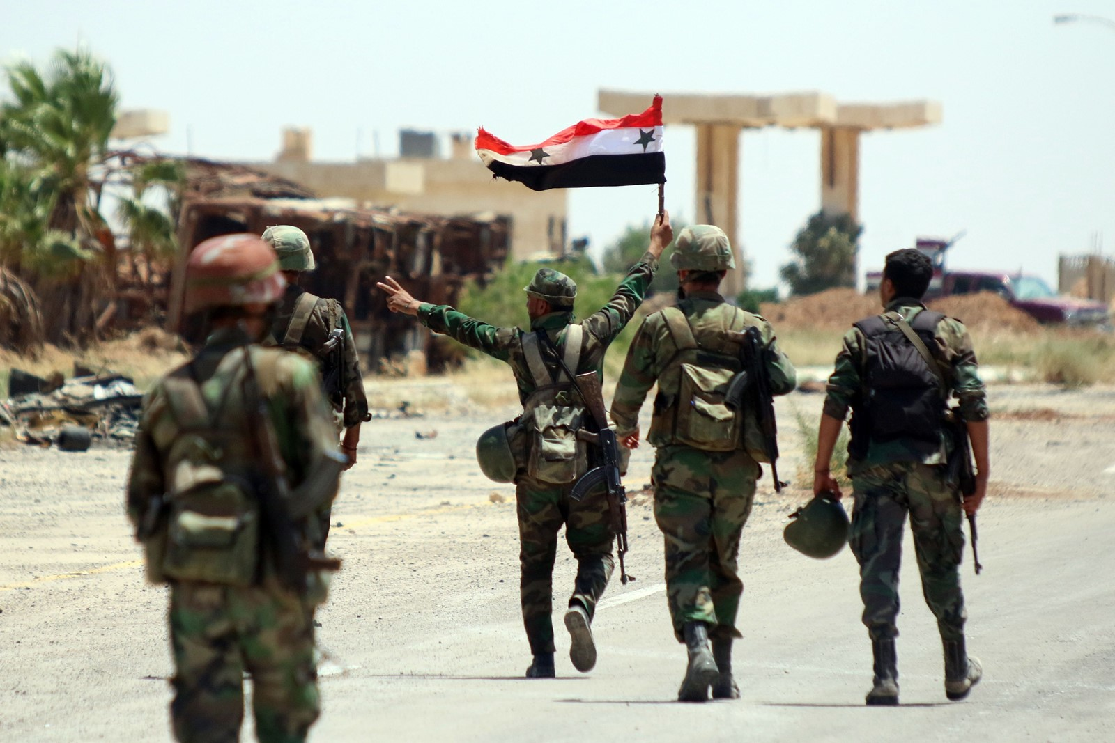 Soldiers brandish the state flag at Syria's Nassib crossing on the southern border with Jordan, the latest victory for the government. — Photograph: Youssef Badawi/European Pressphoto Agency/Shutterstock.